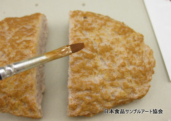 食品サンプルのハンバーグに焼き色を着色しています。